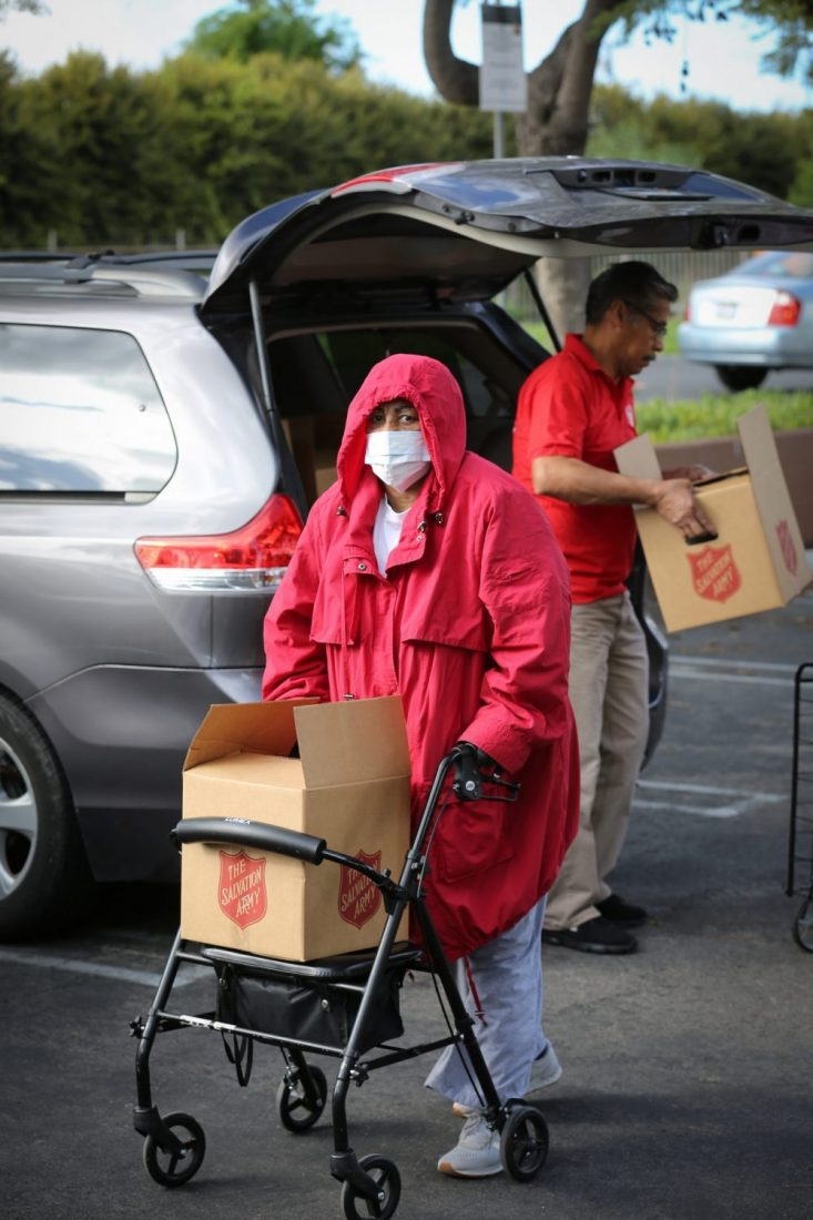 Woman with mask on pushing cart with box in it