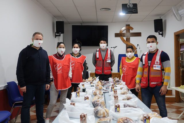 Group of Salvationists with masks on around table