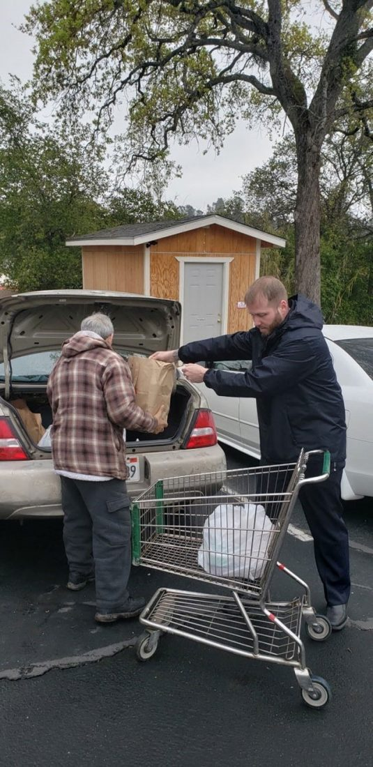 EDS worker helping elderly man with groceries