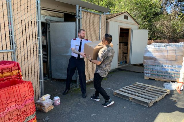 Man handing box to EDS Officer in front of storage area