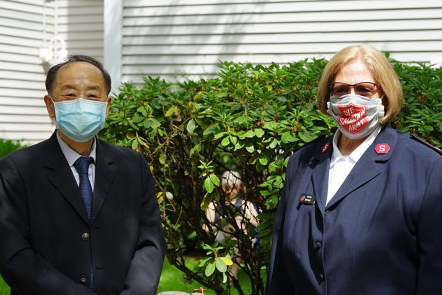 Man and woman in masks standing outside