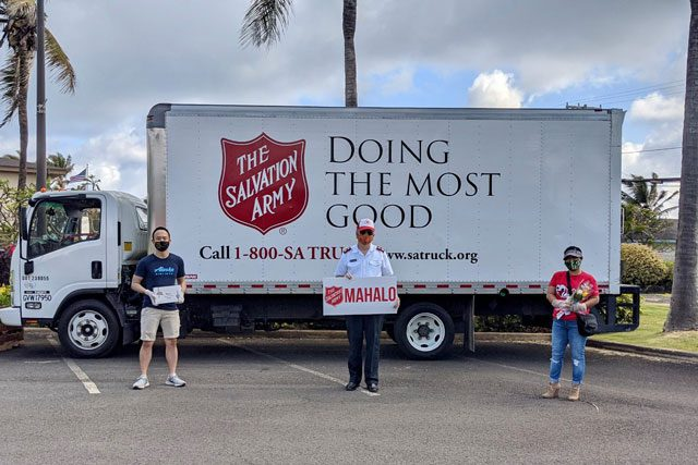 Officer and two volunteers holding sign in front of Salvation Army truck