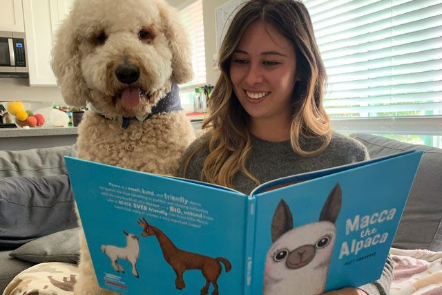 Woman reading book with dog