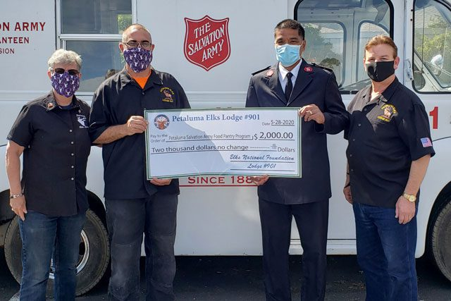 Men with masks holding donation check