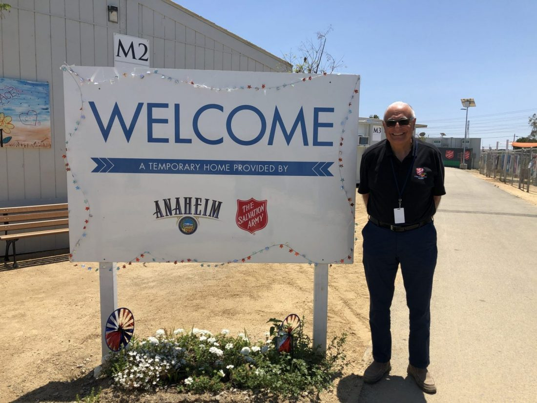 Man standing in front of sign that says welcome