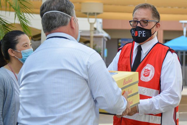 man in mask passing boxes to other man